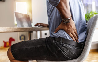man at desk with back pain